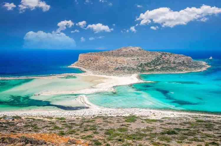 Balos-lagoon-on-Crete-island-Greece.-Tourists-relax-and-bath-in-crystal-clear-water-of-Balos-beach.-min